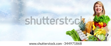 Senior woman with vegetables over blue background. Healthy diet. - stock photo