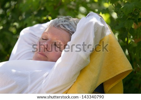 Senior woman with white hairs sleeping on lounger in her garden. - stock photo