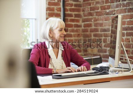 Senior Woman Working At Computer In Contemporary Office
