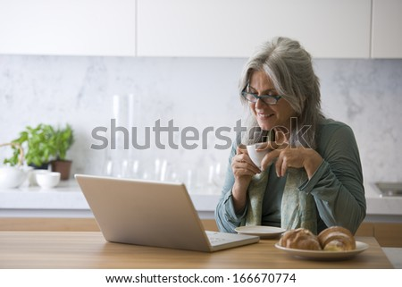 Senior woman working at pc while having breakfast - stock photo