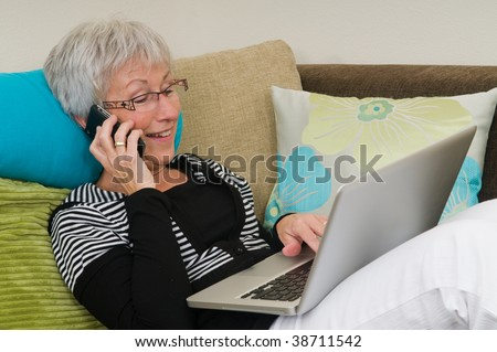 Senior woman working on a laptop, lying relaxed on the couch.