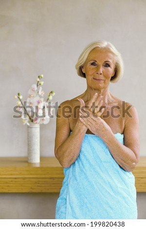 Senior woman wrapped in towel, smiling, portrait - stock photo