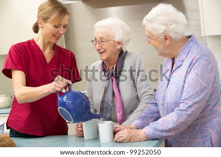 Senior women at home with carer - stock photo