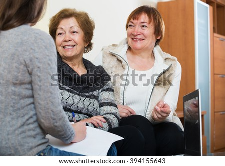 Senior women consulting with banking agent and smiling at a home. Focus on central person