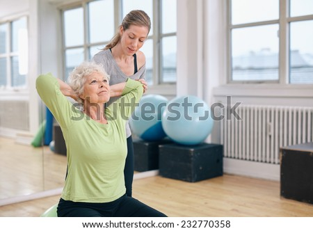 Senior women doing light pilates workout for back muscles with coach assistance. Trainer helping senior woman exercising at gym. - stock photo
