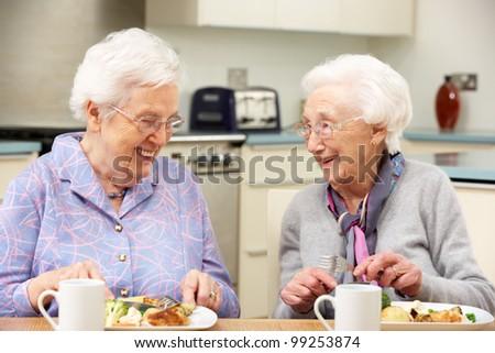 Senior women enjoying meal together at home - stock photo