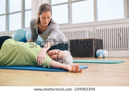 Senior women lying on exercise mat doing stretching workout for back muscles with coach assistance. Female trainer helping elder woman in stretching. - stock photo