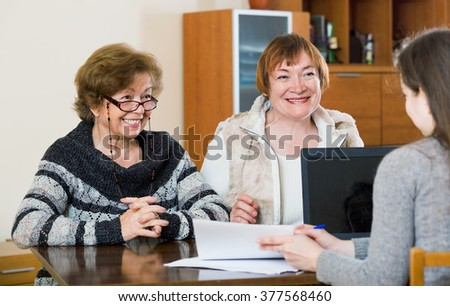 Senior women making will at public notary office and smiling - stock photo