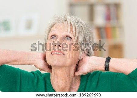Senior women sitting thinking in her living room with her hands clasped behind her neck staring up to heaven with a concerned expression - stock photo