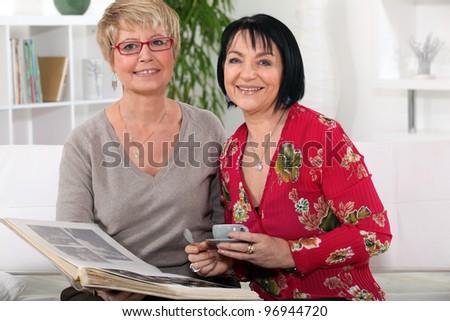 Senior women watching a photo album - stock photo