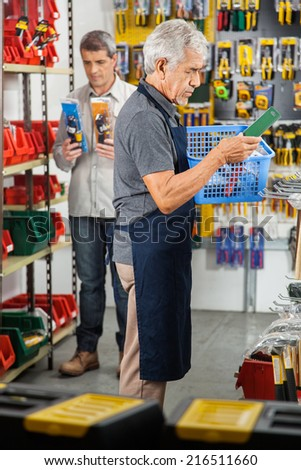Senior worker holding tool basket with customer in the background at hardware store
