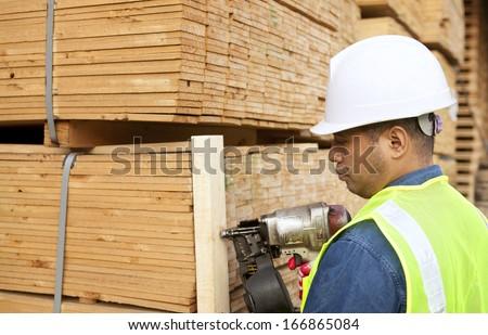 Senior worker nailing timber with nail gun - stock photo