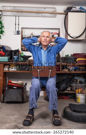 Senior worker relaxing and stretching after work at his workshop. - stock photo