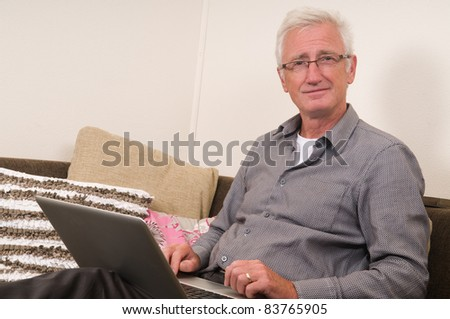 Senior working on a laptop while sitting on the couch - stock photo