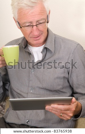 Senior working on a tablet pc while sitting on the couch