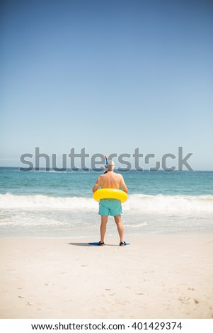 Senioro man with swimming ring and flippers at the beach on a sunny day - stock photo