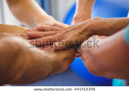 Seniors and fitness instructor putting their hands together in studio