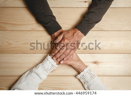 Seniors couple sitting at a wooden table holding hands