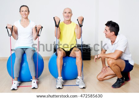 Seniors doing biceps curl on a medicine ball with personal trainer