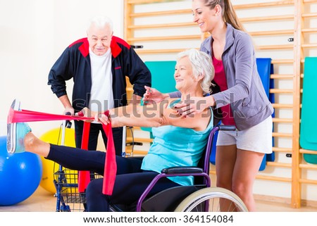 Seniors in physical rehabilitation therapy with trainer - stock photo