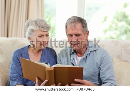 Seniors looking at their photo album at home