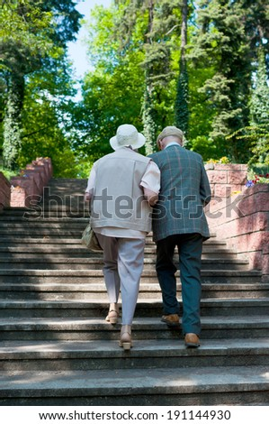 Seniors on the retirement pension are going along stairs through the park - stock photo