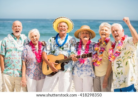 Seniors singing and playing guitar on a sunny day - stock photo
