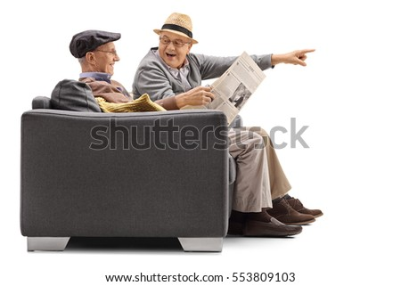 Seniors sitting on a sofa with one of them reading a newspaper and the other pointing isolated on white background