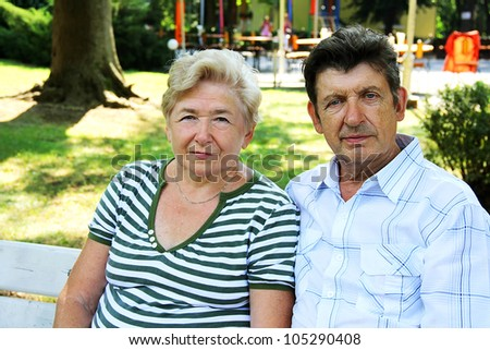 Seniors sitting on bench in park - stock photo