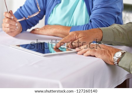 Seniors using the internet with tablet computer and a finger on the touchscreen - stock photo