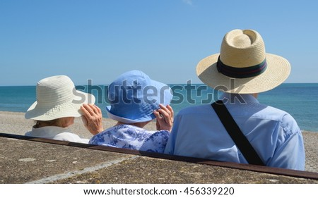 Seniors wearing summer hats on a hot sunny day in Seaton, Devon - stock photo