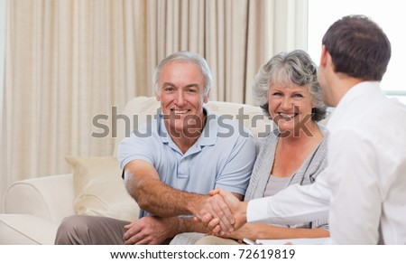 Seniors with assurance man at home - stock photo