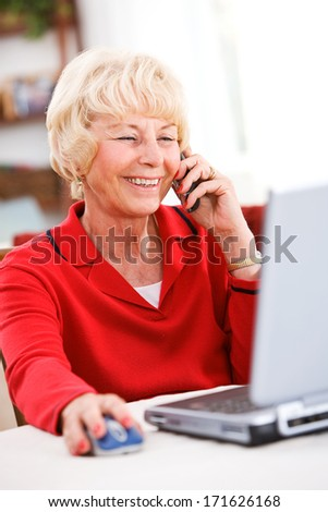 Seniors: Woman On Phone While Using Laptop