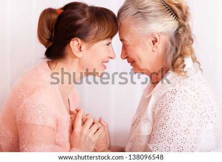 Seniors woman with her caregiver at home - stock photo