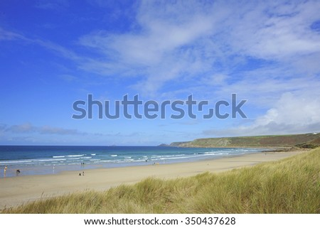 Sennen Cove, a sandy beach on the Atlantic coast with surfers and body boarders enjoying the summer surf, Cornwall, England, United Kingdom - stock photo
