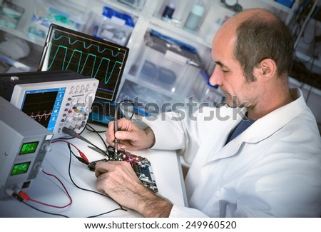 Senor male tech fixes motherboard in computer repair shop. Toned image, shallow DOF, focus on the face of the worker. - stock photo