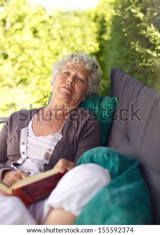 Senor woman sitting on lounge chair with a book and talking a nap. Senior lady sleeping in backyard with a novel - stock photo
