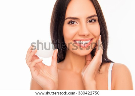 Sensetive pretty woman holding jar of cream and touching her face
