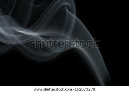 Sensitive incense smoke against black background - stock photo