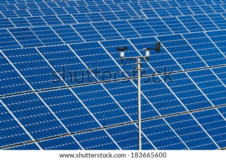 Sensors for wind speed and wind direction on the background of photovoltaic modules - stock photo