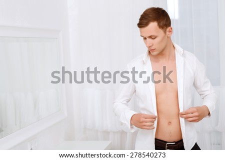 Sensory perception. Handsome muscular man holding shirt that he is wearing against background of white decorated room