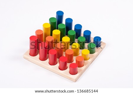 Sensory Toy: Bright Multi-Colored Cylinders on Base - stock photo
