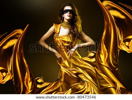 sensual adult woman in golden fabric and mask - stock photo