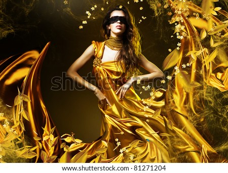 sensual adult woman in golden fabric and mask with leaves - stock photo