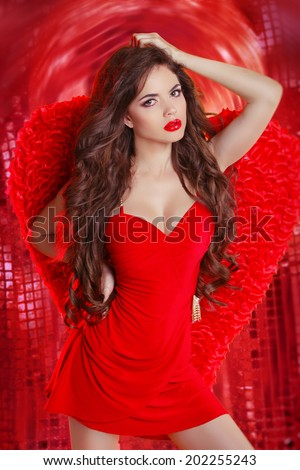 Sensual angel girl in red dancing over disco ball lights party night club background