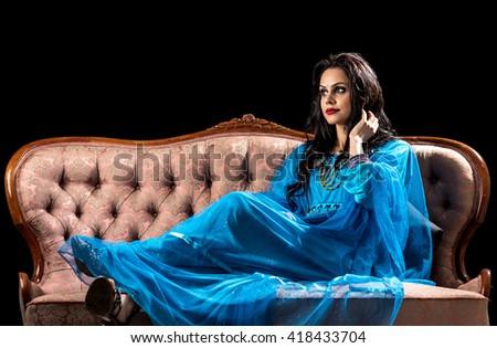 Sensual arabic girl on the retro sofa - stock photo