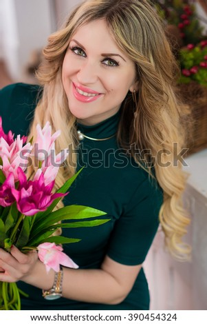 Sensual attractive blonde women posing with bouquet of tulips in the kitchen - stock photo