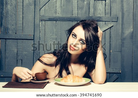 Sensual attractive topless woman with long brunette hair and bright makeup sitting having breakfast of coffee and big burger on wooden background, horizontal picture - stock photo