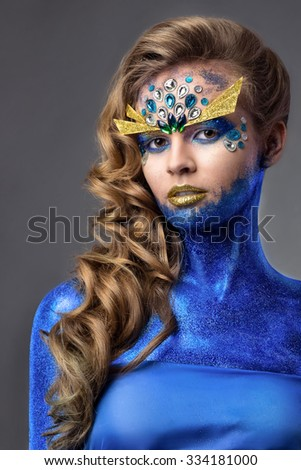 sensual attractive woman in blue glitter, rhinestones on face, golden eyebrows, ocean creature, on grey background - stock photo