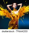 sensual attractive woman in yellow dress and paint splash - stock photo